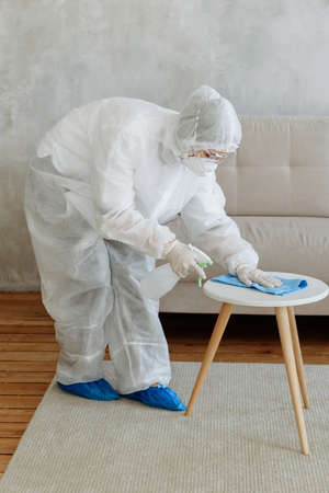 People in a protective suit with a disinfectant spray to disinfect household items and furniture.