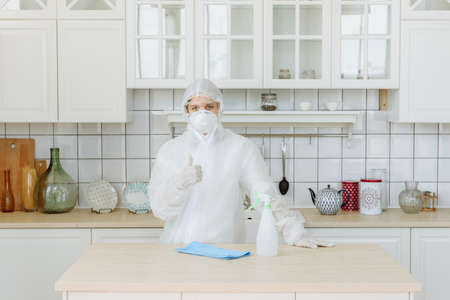 A professional pest or virus contractor stands in the kitchen and shows a positive sign. The concept of a pandemic coronavirus disinfection or COVID-19