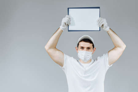 delivery man courier in white uniform gloves and mask on an isolated gray background with a clipboard on his head Stock Photo
