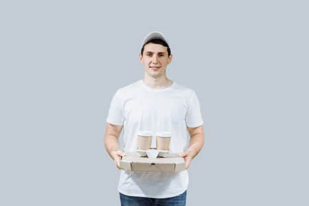 Here is your pizza! Cheerful young delivery man holding out pizza box and coffe isolated on gray background. courier copy space