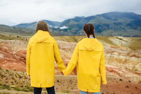 Two happy girls, tourists, holding each other's hands in yellow djeviks, look at the colored mountains. Travel and vacation concept. Autumn weather