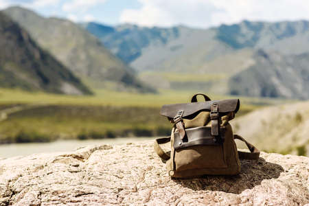 A hipster brown travel backpack. View from the front of the bag against the background of mountains. Traveler on vacation, blank blurred mock up for text