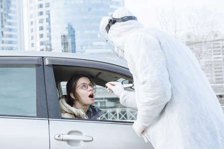 A virologist or medical doctor wearing PPE hazmat protective clothing takes a sample of a PCR test with a cotton swab from a female driver in her car. Mobile testing concept for Covid-19 coronavirus