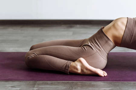 woman exercising balance in yoga standing on mat in the room