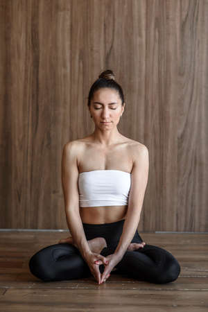 sportive woman practicing yoga in the gym
