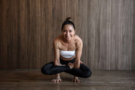 athletic muscular woman practicing yoga and pilates stretching on the floor
