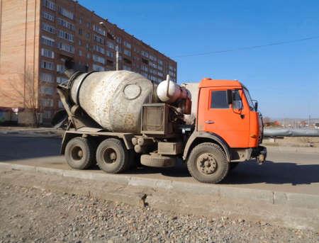 Concrete mixer on the street. Construction engineering. Orange truck. Blue sky. Ust-Kamenogorsk (Kazakhstan)