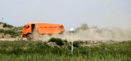 An orange truck is rushing along the dusty road 写真素材