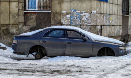 Abandoned car without wheels. City outskirts. Grunge background 写真素材