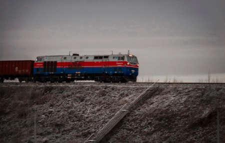 Kazakhstan, Ust-Kamenogorsk, october 31, 2018: Freight train. Grunge Landscape. Locomotive ТE33А. The TE33A is a type of diesel locomotive developed by GE Transportation Systems 報道画像