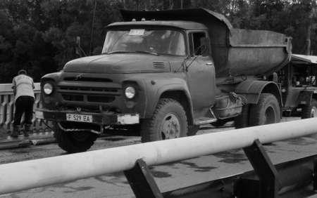 Kazakhstan, Ust-Kamenogorsk, august 25, 2018: Old dump truck ZIL 130. Road reconstruction works. Worker