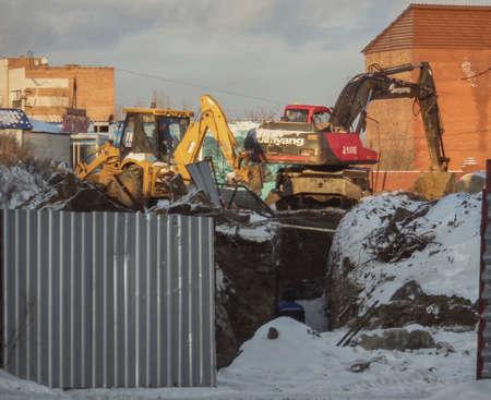 Kazakhstan, Ust-Kamenogorsk, december, 2018: Two excavators work on construction site