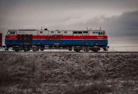 Kazakhstan, Ust-Kamenogorsk, october 31, 2018: Freight train. Grunge Landscape. Locomotive ТE33А. The TE33A is a type of diesel locomotive developed by GE Transportation Systems 新闻类图片