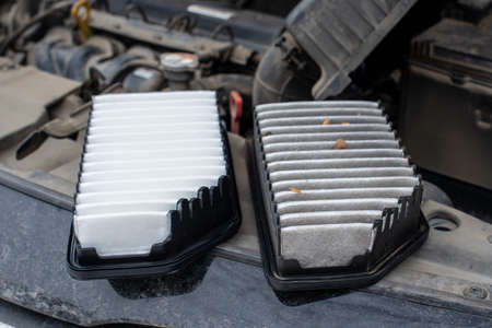 Replacing the car engine air filter. The photo shows an old dirty filter and a new one. The filters are located on the engine compartment of the car.