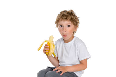 The little boy peeled a banana and took a big bite, holds it in his mouth and tries to chew. The gaze is directed to the camera. Photo is taken on a white isolated background. The boy is wearing a plain white T-shirt.