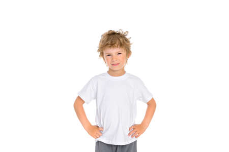 A little boy shows his displeasure with his facial expression and holding his hands at his waist. Photo of a boy on a white background.