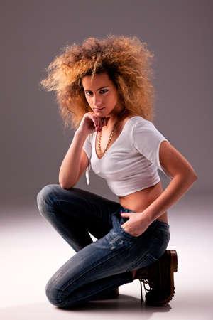 woman kneeling: beautiful ans attractive woman kneeling, studio shot Stock Photo