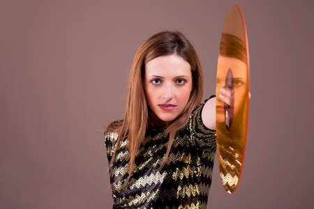 beautiful blonde woman standing holding a golden vinyl disc,  studio shot photo