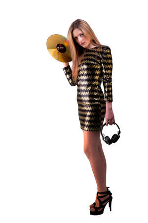 beautiful blonde woman standing holding a golden vinyl disc, and headphones, isolated on white background, studio shot photo