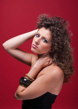 young and beautiful woman, with curly hair, holding her neck, on red background, studio shot photo