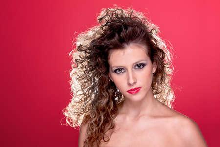 mujer hermosa con el pelo rizado, con luz por detrás, en rojo, tiro del estudio Foto de archivo - 16251060