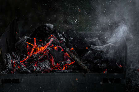 Burning coals in the grill, flame and smoke. Foto de archivo