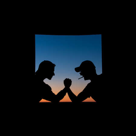 Silhouette of friends doing a showdown at the edge of a window during the sunset 写真素材