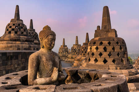 Breathtaking view of the sunrise from the meditating Buddha statue and stone stupas against a bright sun. The ancient Buddhist temple of Borobudur