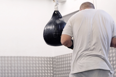 Boxer in a light T-shirt beats blows on a black pear in the training hall Stock Photo