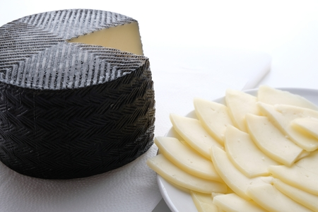 creamery: The chopped cheese lies on a plate next to the round head of the cheese. Cheese in black wax lies on a white cutting board Stock Photo