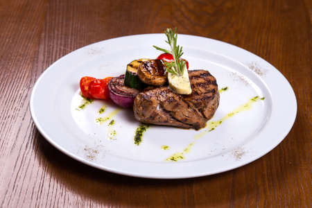 thick steak with rosemary and fried vegetables cheese on white plate Stock Photo