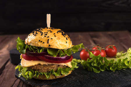 Homemade vegetarian burger with cutlet, tomato, cheese, green salad and purple onion on a dark wooden background