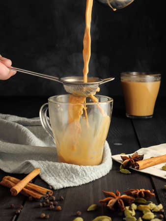 Masala tea is poured through a sieve into a glass mug. Species are on the table. Reklamní fotografie