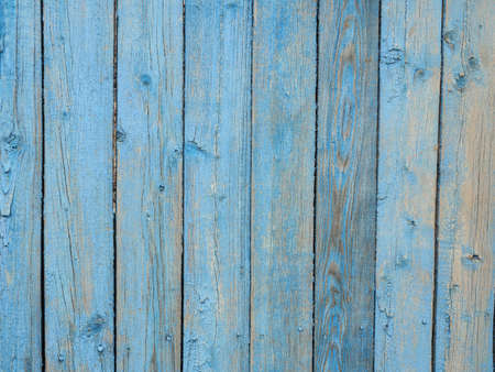 Old wooden planks covered with peeling blue paint.