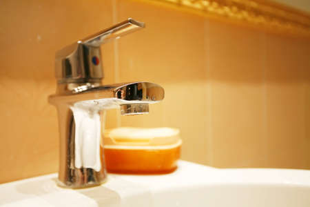 water tap in a bathroom on a orange background photo