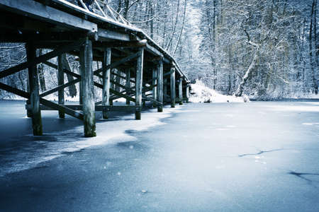 Winter landscape. Old wooden bridge under river.