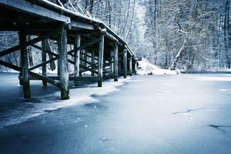 Winterlandschaft. Alte h�lzerne Br�cke unter Fluss. Lizenzfreie Bilder