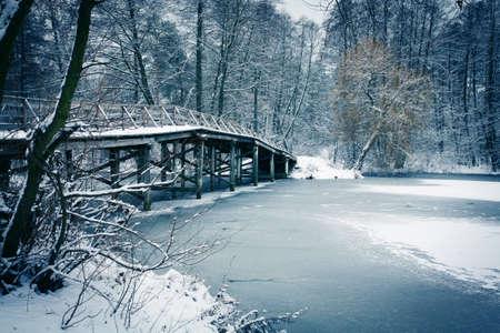 Winter landscape. Old wooden bridge under river. photo