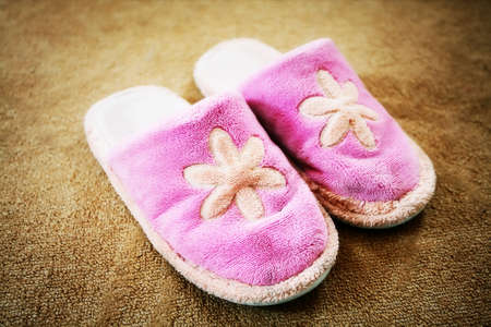 Pink slippers stay in the room on a carpet. photo