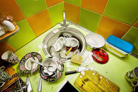 messy kitchen: washing-up in kitchen, green and orange tiles on a wall