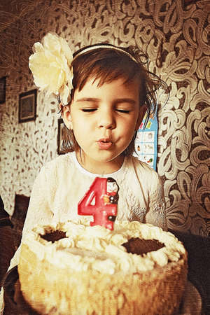 girl blowing: happy birthday. little girl blow out the cake