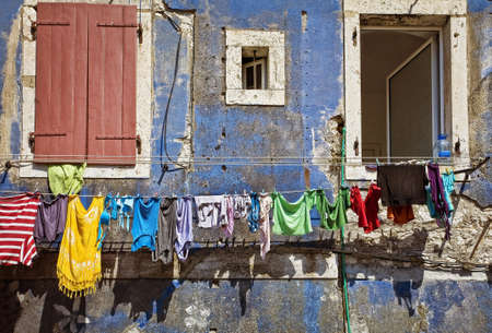 clean clothing on a rope. blue wall with windows photo