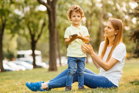 Mother and her baby, play cheerfully in the smartphone, outdoors