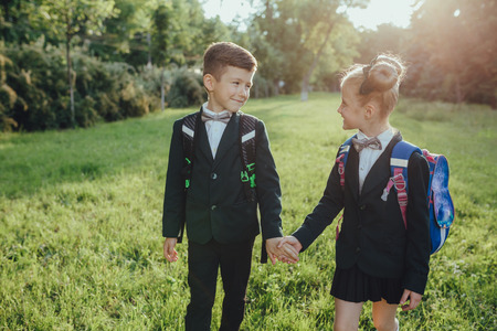 two schoolchildren are holding their hands, with schoolbag, dressed in school uniform, outdoor, at sunset