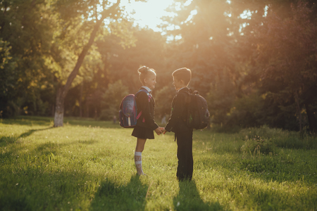 schoolchildren, little boy and little girl dressed in school uniform with schoolbag, holding hands, outdoor, at sunset