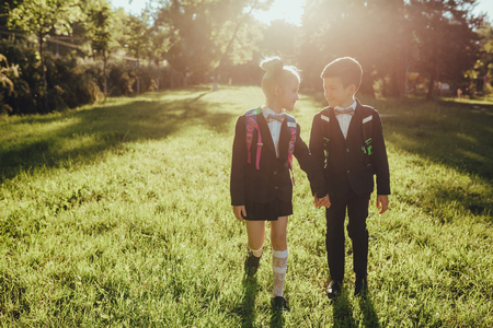 two enthusiastic schoolboys and schoolgirll head to school, outdoor, at sunset