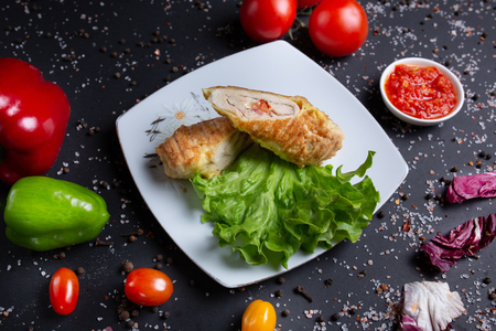 chicken roll with red sauce, on black background with red tomatoes, bread, red green peppers and broccoli, top view