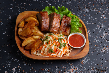 fried potatoes with baked meat and salad, on black background, top view Stock Photo