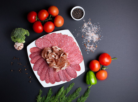 plate of sausage and meats, on black background with tomatoes, dill, garlic and broccoli, top view