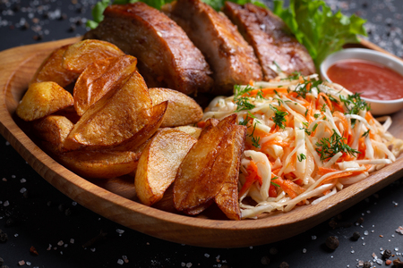 french fries with meat and salad, on black background, top view
